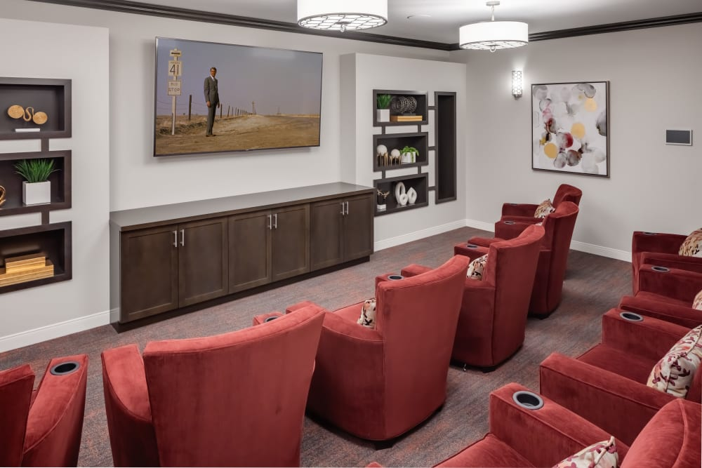 Theater area with rows of velvet red seats at Aspired Living of La Grange in La Grange, Illinois