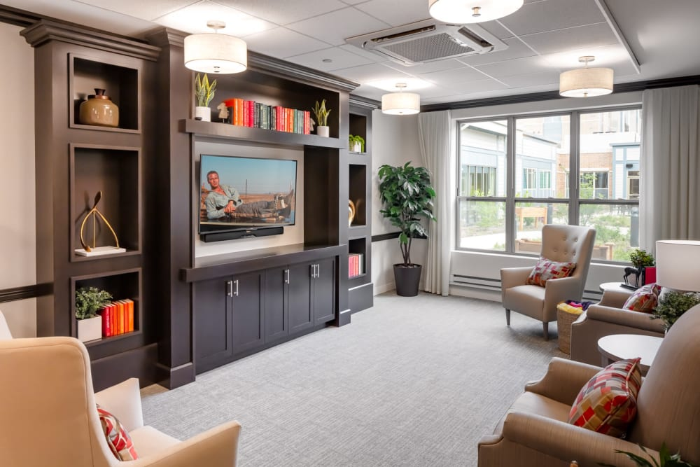 Tv lounge with a row of plush chairs at Aspired Living of La Grange in La Grange, Illinois