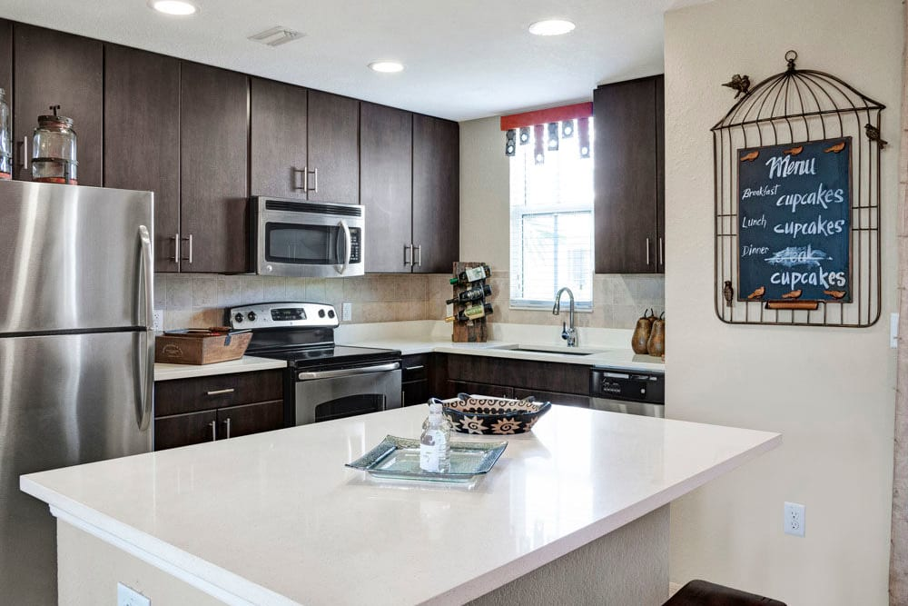 A kitchen island and stainless steel appliances are features of this kitchen in an apartment at City Center on 7th Apartment Homes in Pembroke Pines, Florida