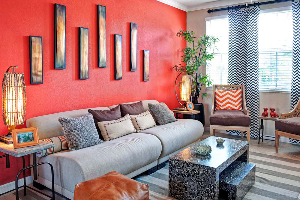 Well decorated living room with red accent wall and couch seating at City Center on 7th Apartment Homes in Pembroke Pines, Florida