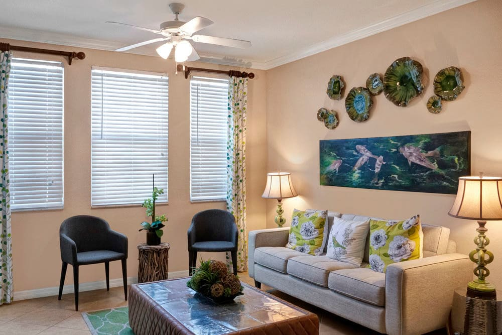 Living room with art on the walls, ceiling fan, couch and chairs  at City Center on 7th Apartment Homes in Pembroke Pines, Florida