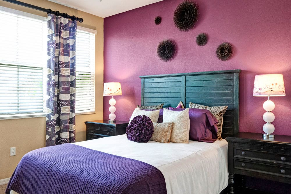 Bedroom with colorful accent wall and large windows at City Center on 7th Apartment Homes in Pembroke Pines, Florida
