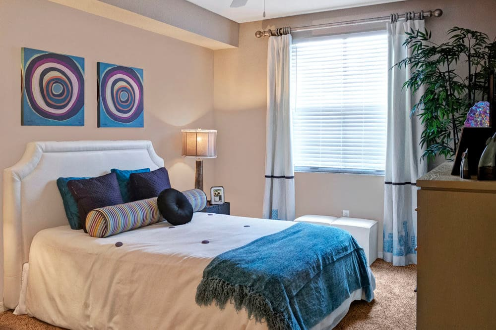 Comfortable bedroom featuring large window for ample natural light at City Center on 7th Apartment Homes in Pembroke Pines, Florida