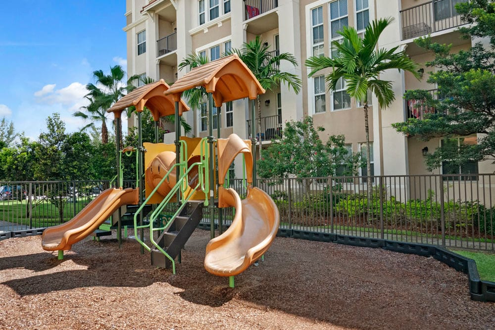 Playground equipment with apartment building in the background at City Center on 7th Apartment Homes in Pembroke Pines, Florida