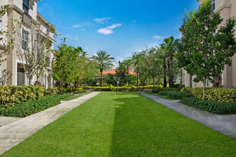 Sidewalks by well manicured lawn outside apartment building at City Center on 7th Apartment Homes in Pembroke Pines, Florida