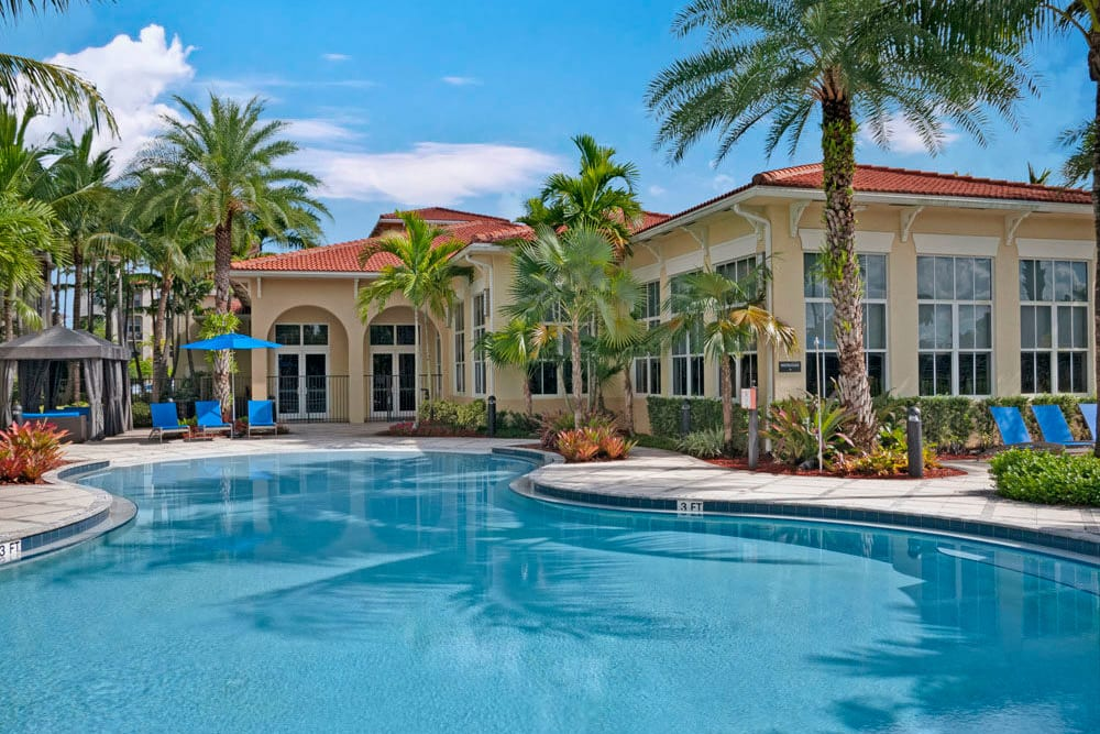 Well manicured grounds by the community pool at City Center on 7th Apartment Homes in Pembroke Pines, Florida