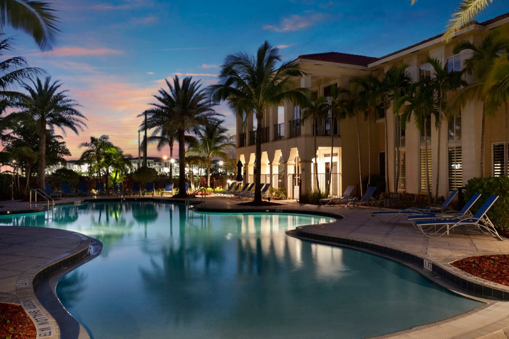 Community pool with palm trees at sunset at City Center on 7th Apartment Homes in Pembroke Pines, Florida