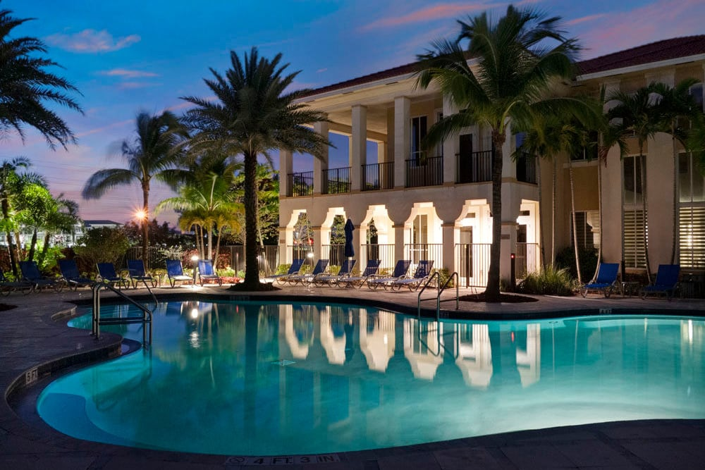 Outdoor community pool lit up at night at City Center on 7th Apartment Homes in Pembroke Pines, Florida