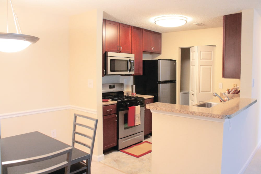 View of kitchen from dining area in an apartment at The Commons At Haynes Farm in Shrewsbury, Massachusetts