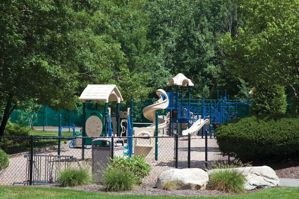 Mature trees surround the playground equipment at The Commons At Haynes Farm in Shrewsbury, Massachusetts