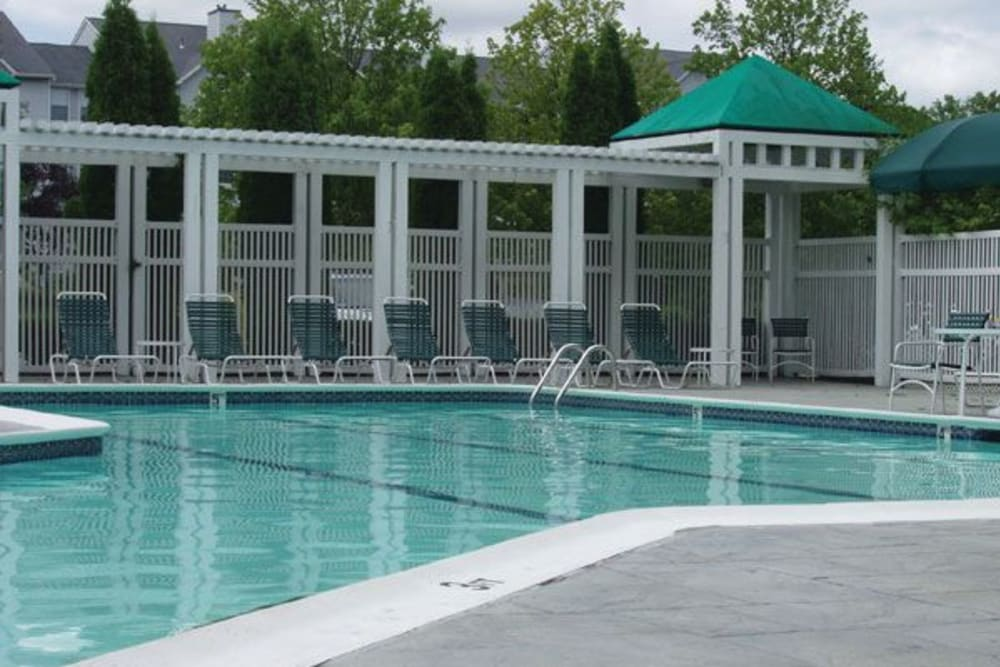 Outdoor community pool with lounge chairs at The Commons At Haynes Farm in Shrewsbury, Massachusetts