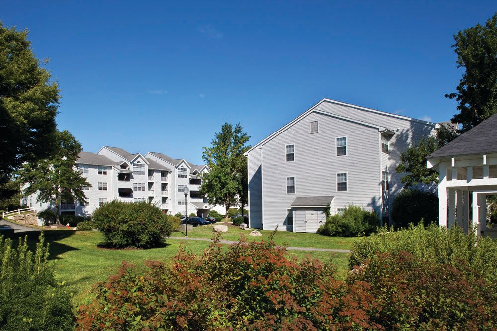 Well-maintained landscaping outside of apartment buildings at The Commons At Haynes Farm in Shrewsbury, Massachusetts