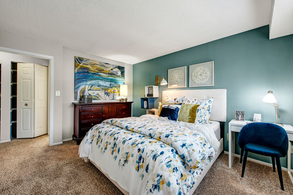 Bedroom with green accent wall and plush carpet at Country Village Apartments in Bel Air, Maryland