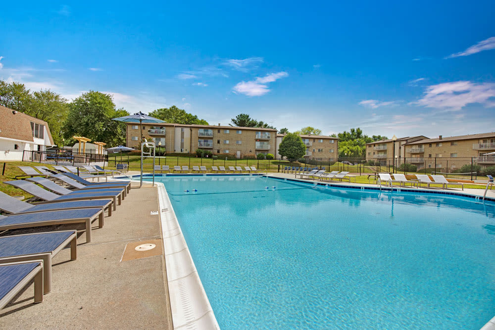 Lounge chairs next to community pool with blue sky in the background at Country Village Apartments in Bel Air, Maryland