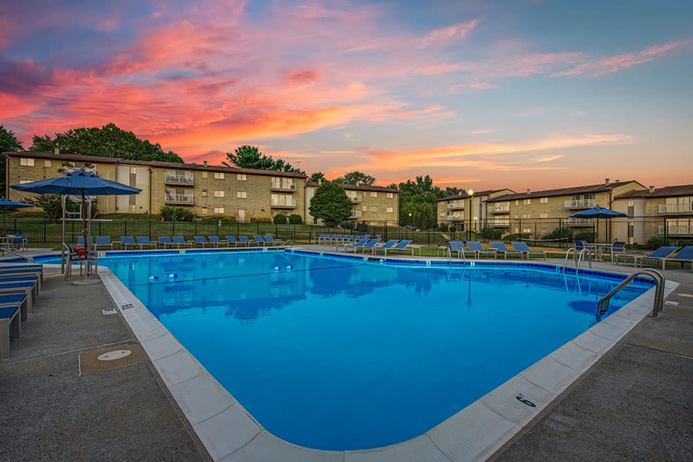Brightly colored clouds at sunset over the apartment buildings in the background by the pool at Country Village Apartments in Bel Air, Maryland
