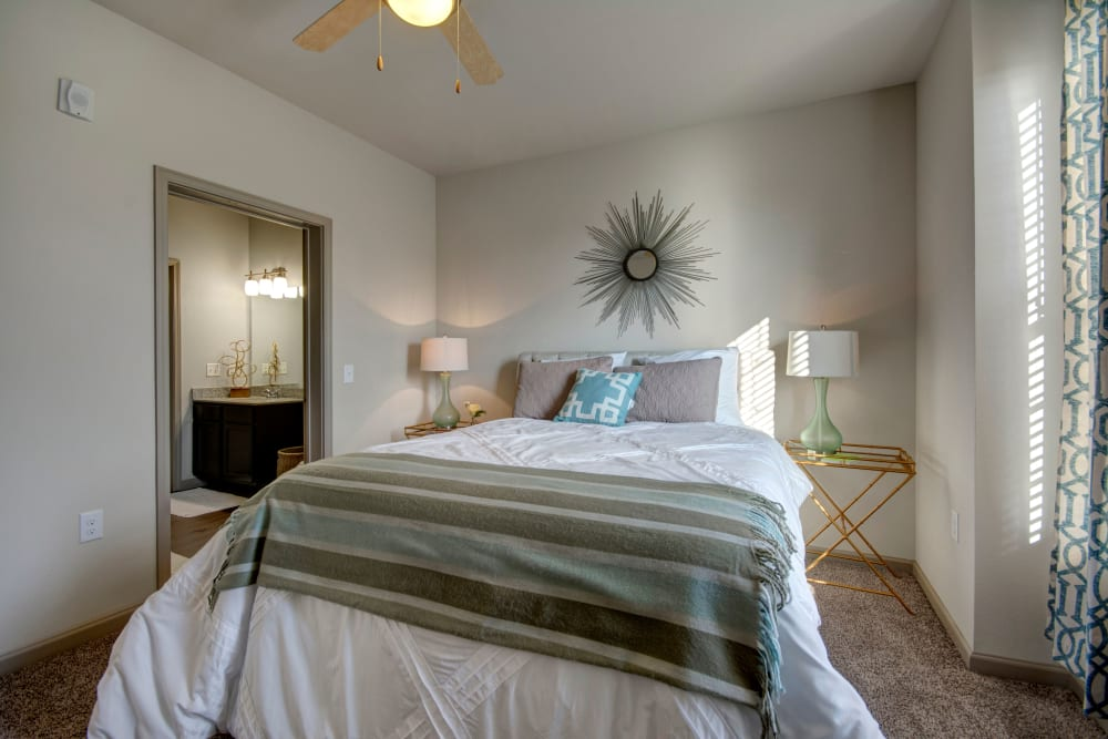 Comfortable bedroom with long white curtains and stylish bedding at Creekside South in Wylie, Texas