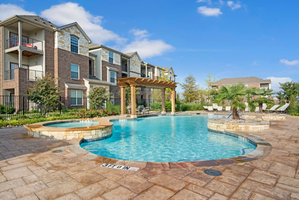 Community pool with apartments in the background at Creekside South in Wylie, Texas