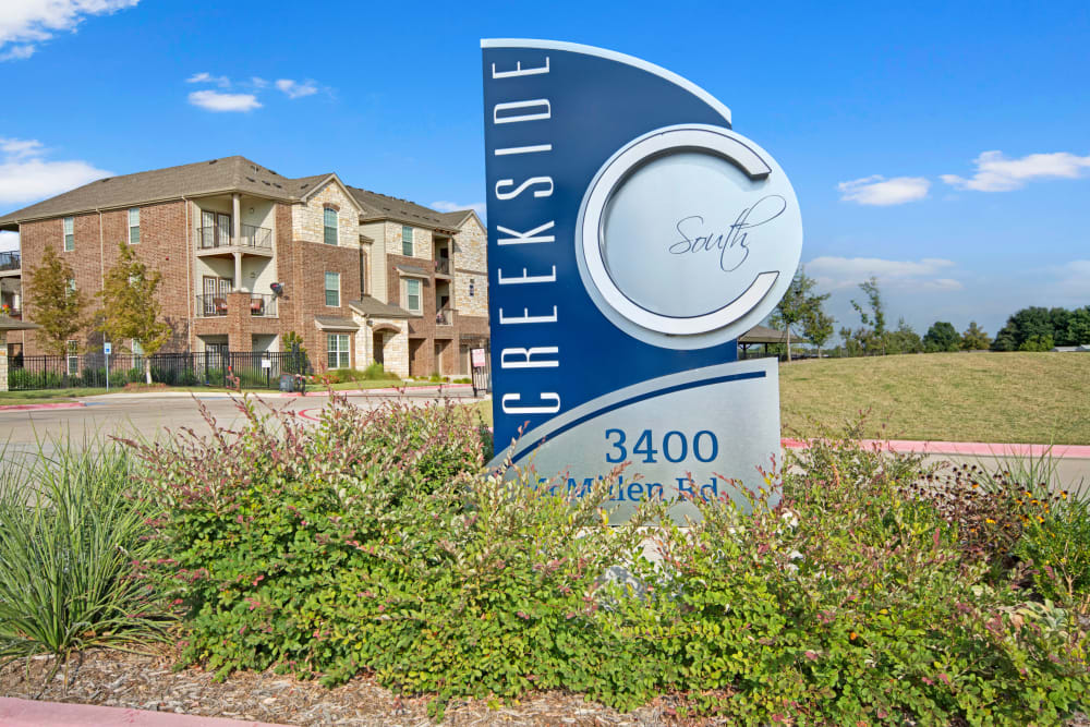 Community sign with apartment buildings in the background at Creekside South in Wylie, Texas
