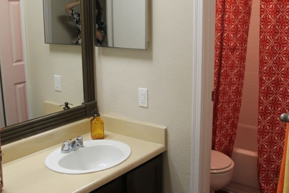 Model bathroom with large vanity mirror and oval tub at The Reserve at Windmill Lakes in Houston, Texas
