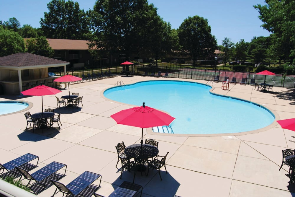 Shaded lounge chairs poolside at Racquet Club Apartments and Townhomes in Levittown, Pennsylvania