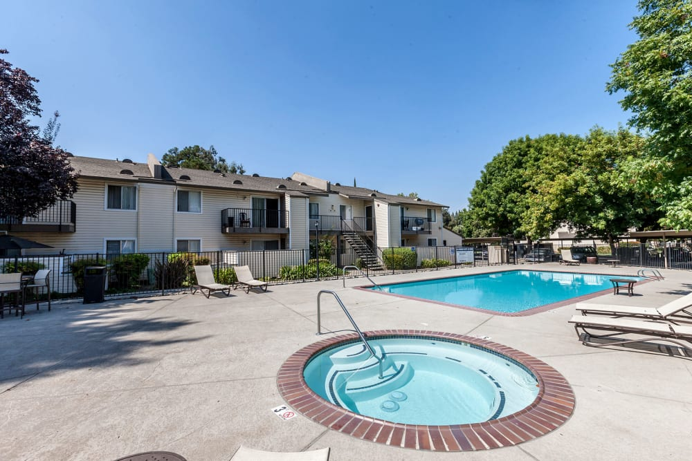 Outdoor hot tub and swimming pool at The Woodlands Apartments in Sacramento, California
