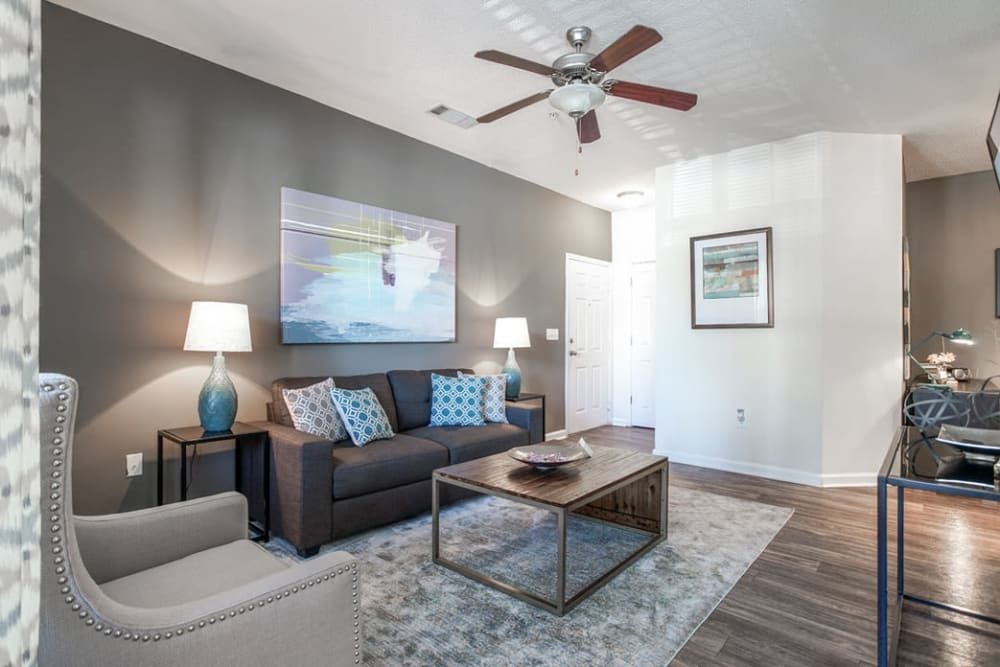 Living room featuring a ceiling fan and couch seating  at Eastwood Village in Stockbridge, Georgia