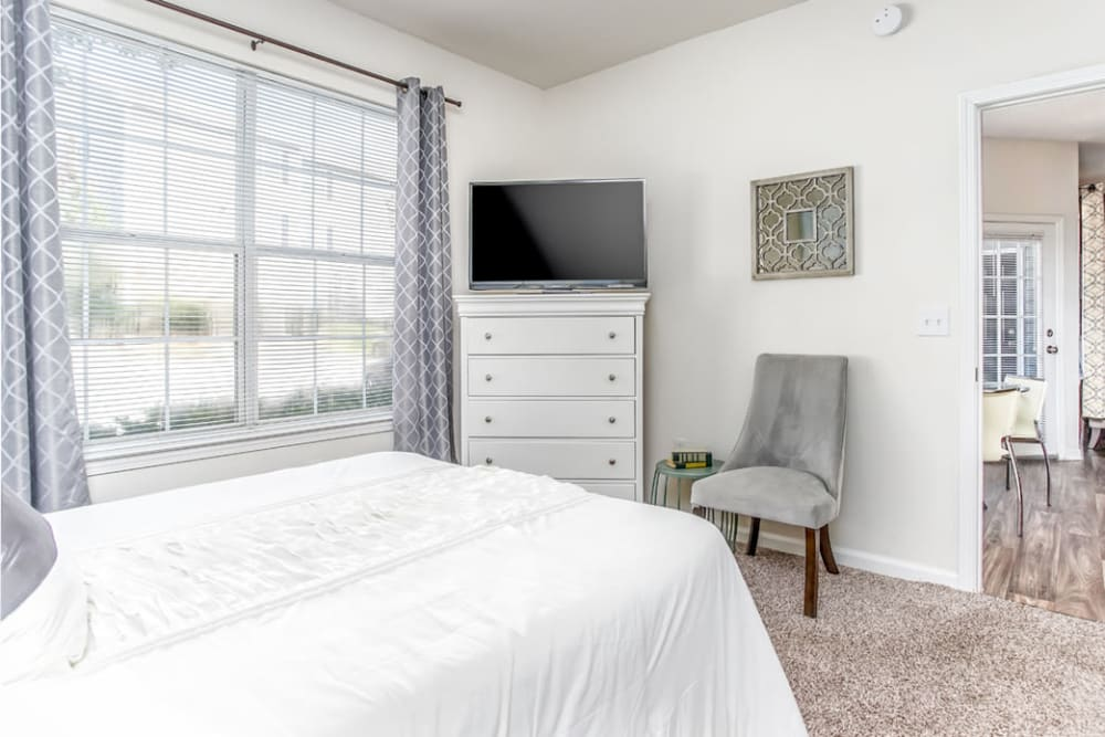 Large windows offer a Naturally light and bright bedroom space at Eastwood Village in Stockbridge, Georgia