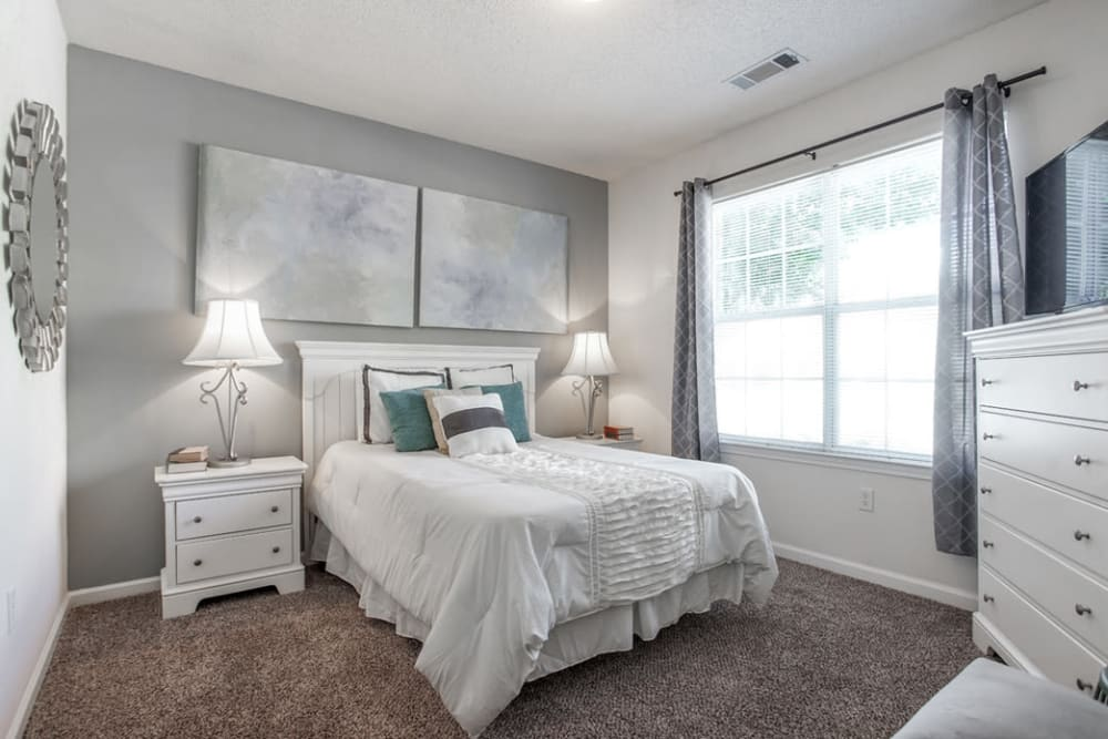 Well decorated bedroom featuring a large window for natural light at Eastwood Village in Stockbridge, Georgia