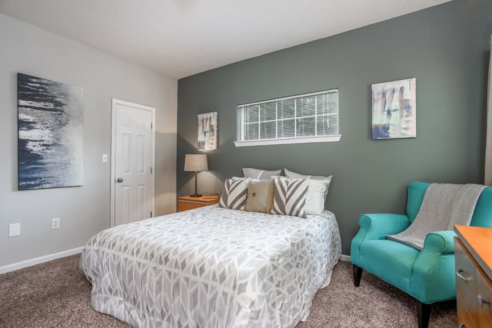 Well lit model bedroom with decorative chair at Peachtree Landing in Fairburn, Georgia