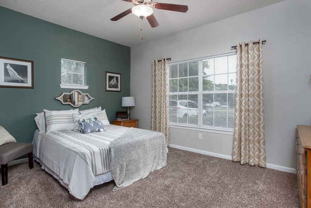 Well decorated model bedroom with ceiling fan at Peachtree Landing in Fairburn, Georgia