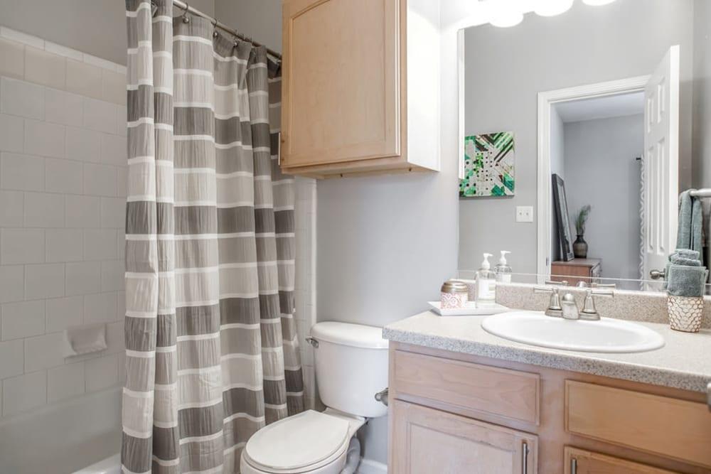 Model bathroom with large vanity mirror and oval tub at Peachtree Landing in Fairburn, Georgia