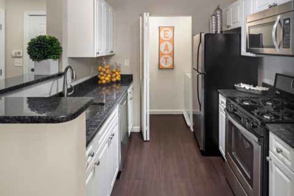 Kitchen featuring black appliances in ample countertop space at Ellington Metro West in Westborough, Massachusetts