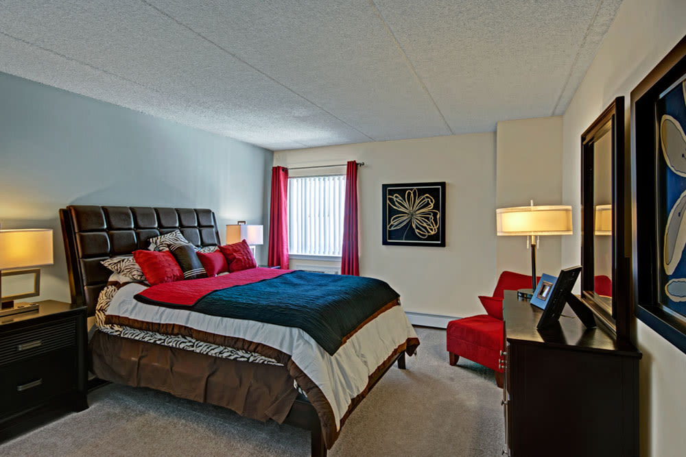 Well decorated bedroom with hutch and red accent curtains at Frazer Crossing in Malvern, Pennsylvania