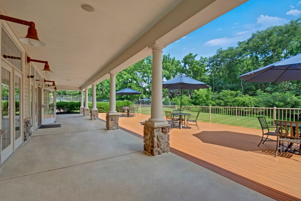 Covered patio space outside clubhouse  at Frazer Crossing in Malvern, Pennsylvania also features a deck with tables, chairs and sun shade umbrellas