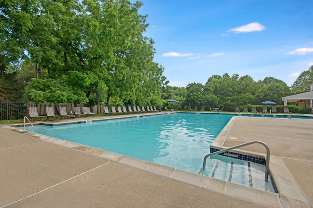 Community pool at Frazer Crossing in Malvern, Pennsylvania is lined by mature trees and features lounge chair seating
