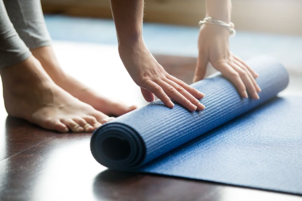 Resident rolling up their yoga mat at RISE at Riverfront Crossings in Iowa City, Iowa
