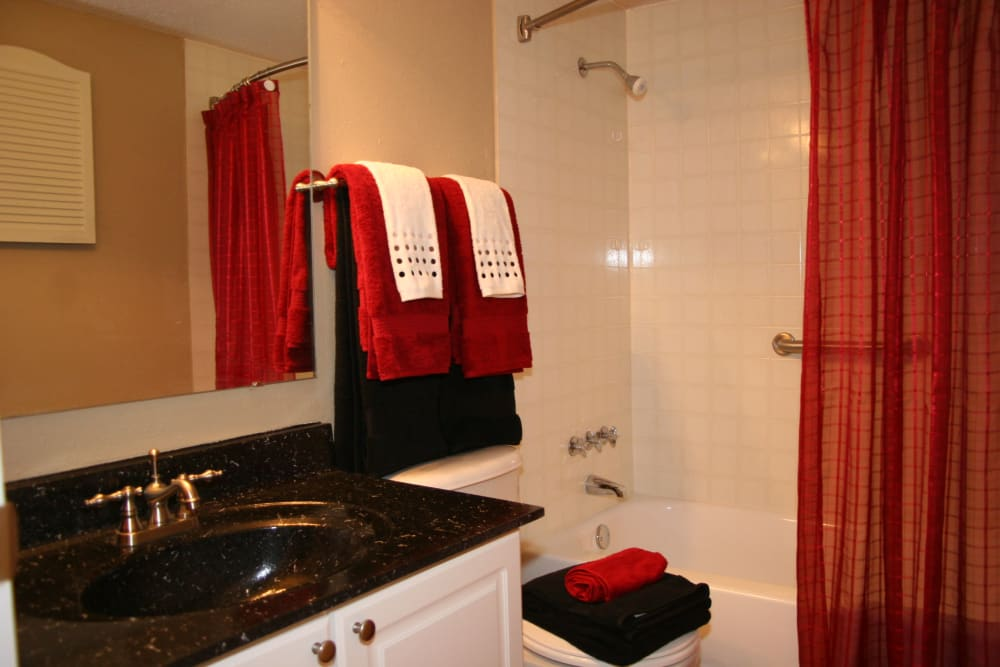 Model bathroom with large vanity mirror and oval tub at Oxford Hills in St. Louis, Missouri