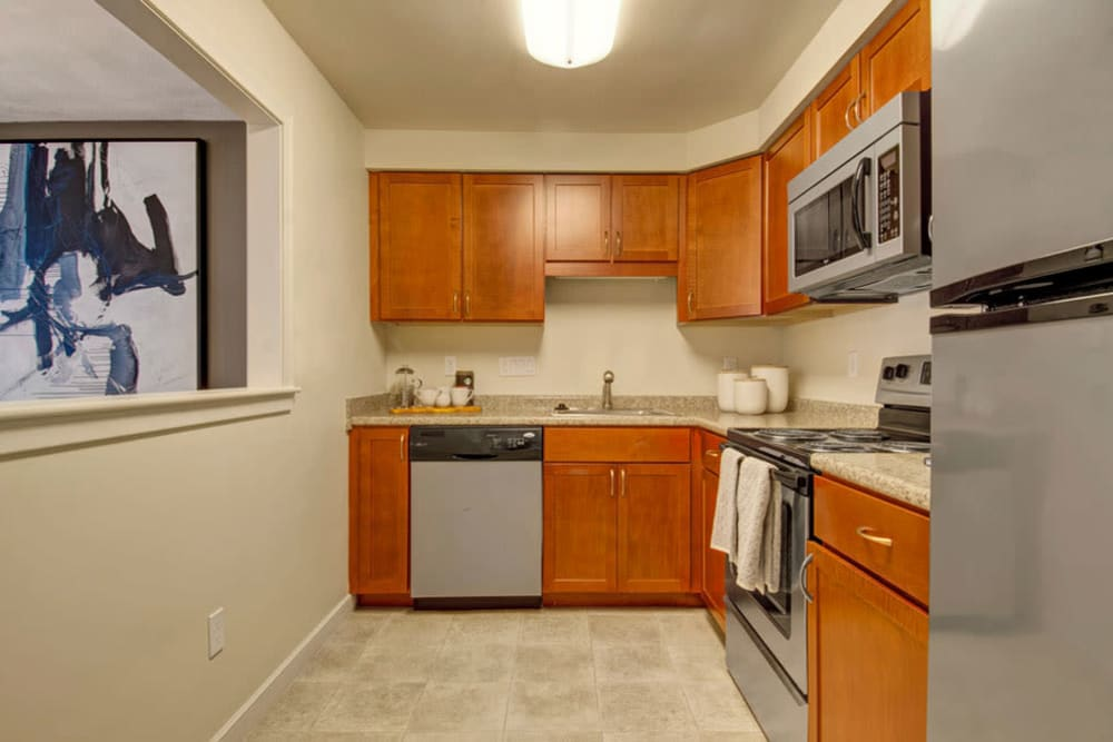 Spacious kitchen with open wall that looks out onto living room in an apartment at Gardencrest in Waltham, Massachusetts
