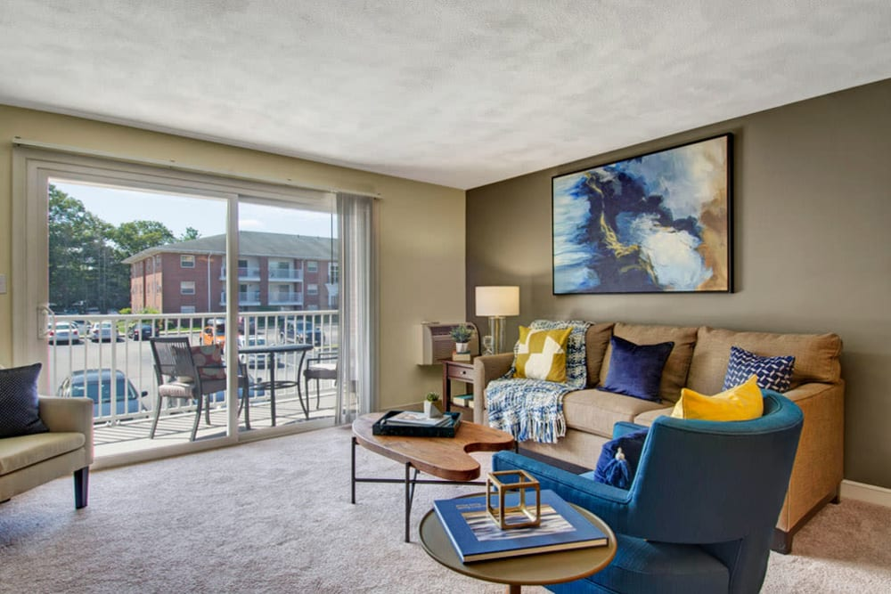 This is living room with sliding glass doors leading to outside at Gardencrest in Waltham, Massachusetts