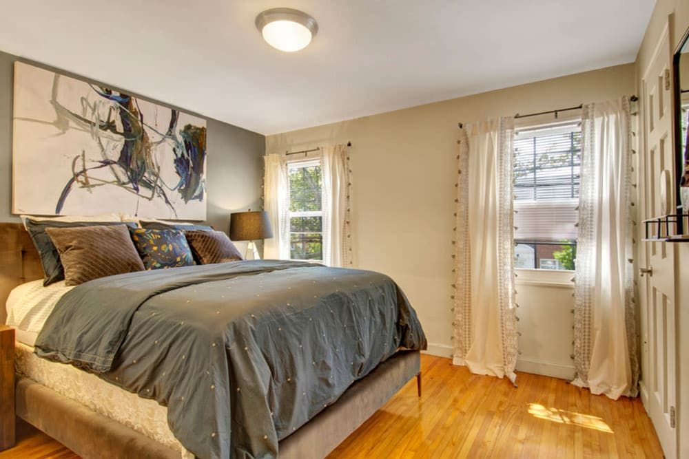 Bedroom with large painting hanging over the bed in an apartment at Gardencrest