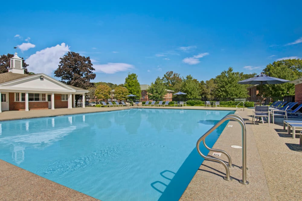 Beautiful outdoor community pool with clubhouse in the background at Gardencrest in Waltham, Massachusetts