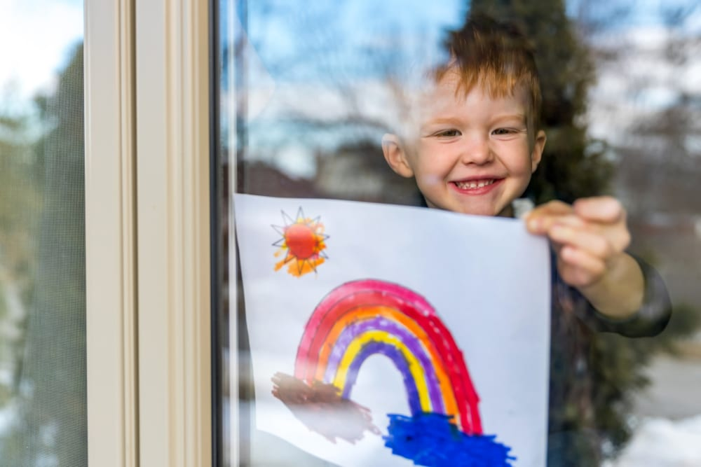 Happy child proudly taping his painting to the window of their home at Alturas Embry Hills in Doraville, Georgia