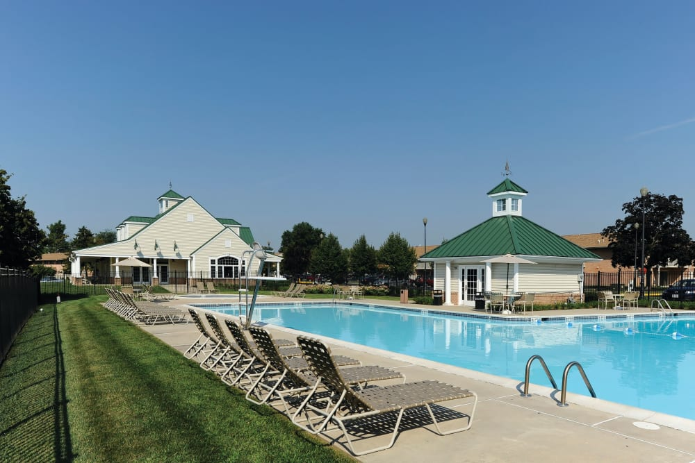 Lounge chairs and grassy area besides community pool at Golf Club Apartments in West Chester, Pennsylvania