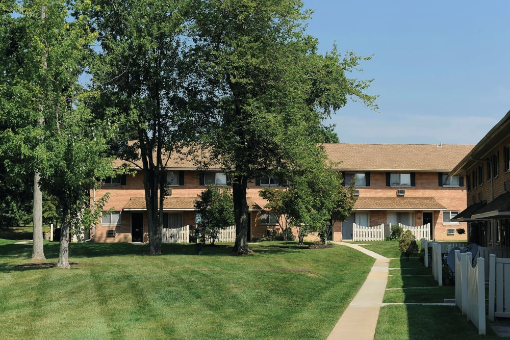 Exterior of apartments at Golf Club Apartments in West Chester, Pennsylvania with grassy field of mature trees