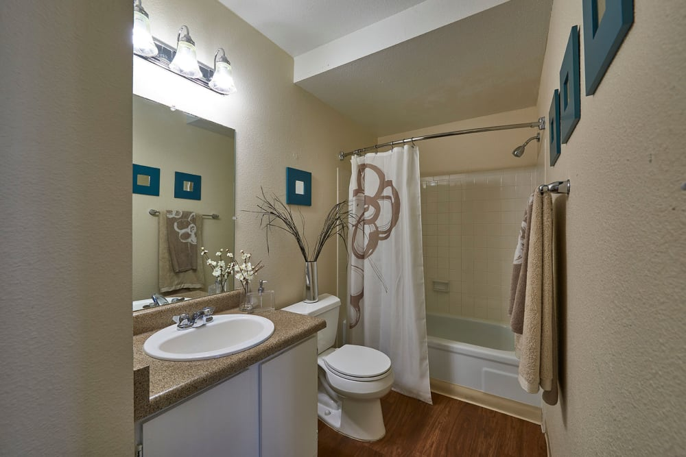 Bathroom at Hampden Heights Apartments in Denver, Colorado features a large vanity, bright light fixture and a shower bathtub
