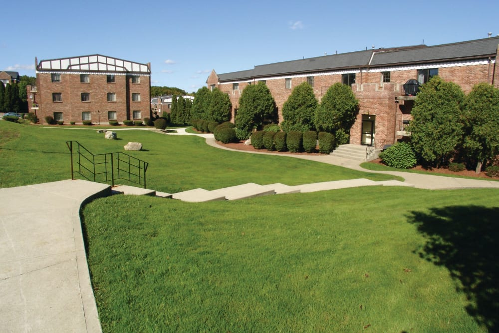 Walkways and grassy field outside of apartment buildings at The Heights At Marlborough in Marlborough, Massachusetts