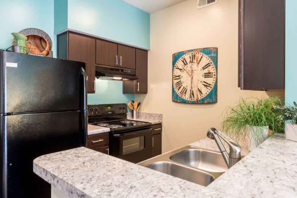Kitchen featuring black appliances and double sink at Heritage Green in Hilliard, Ohio
