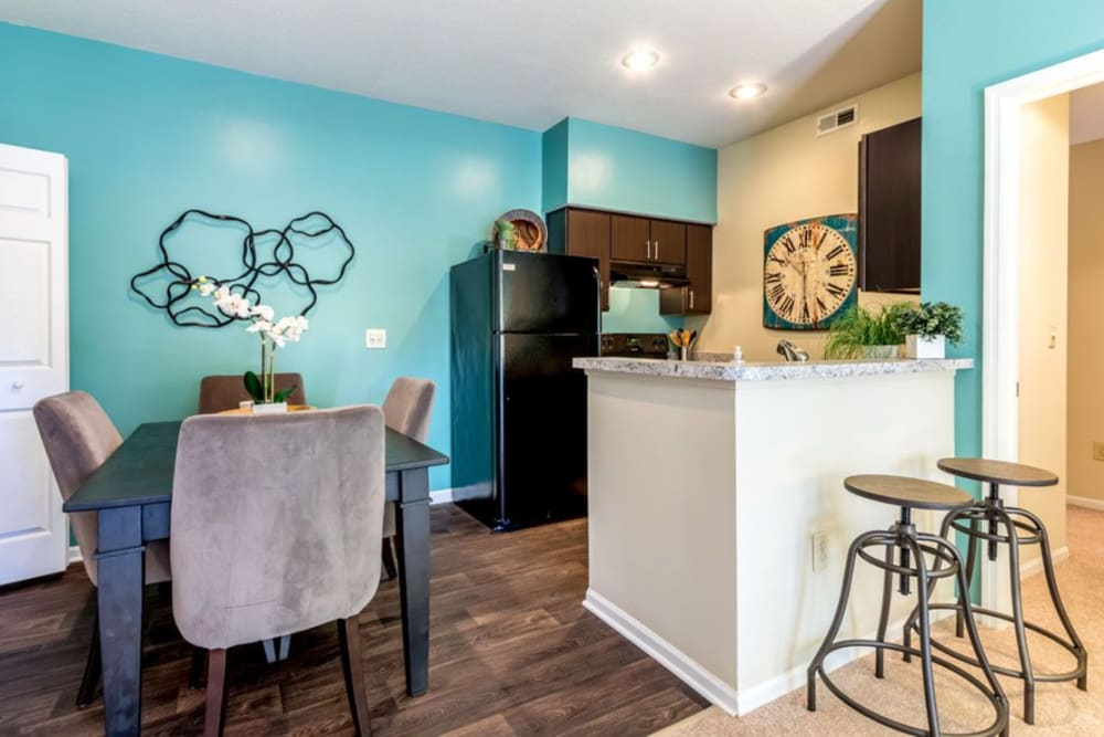 Bright blue green painted accent wall in dining space outside of a kitchen In an apartment at Heritage Green in Hilliard, Ohio