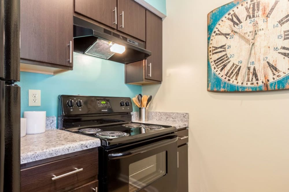 Dark wood cabinets and black appliances in a kitchen at Heritage Green in Hilliard, Ohio