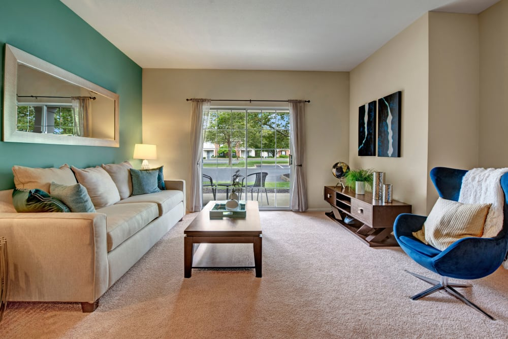 Spacious living room featuring green accent wall and sliding glass doors leading to outside at Heritage Green in Hilliard, Ohio